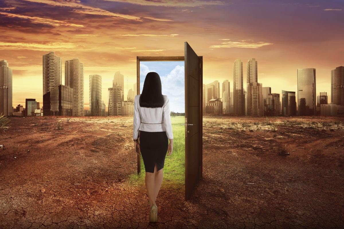 business woman walking to the open wooden door